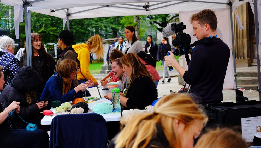 A young man films people making at a crowded table outdoors.