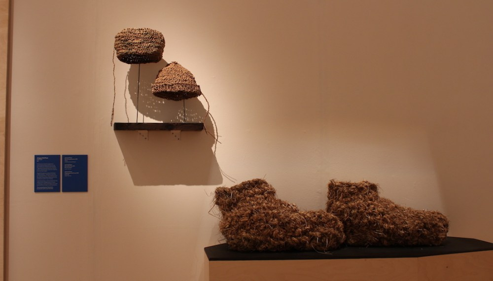 woven hats and large woven boots on plinth