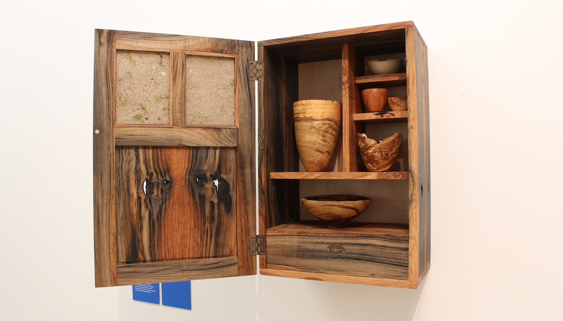 wooden cupboard on shelves with wood turned items inside