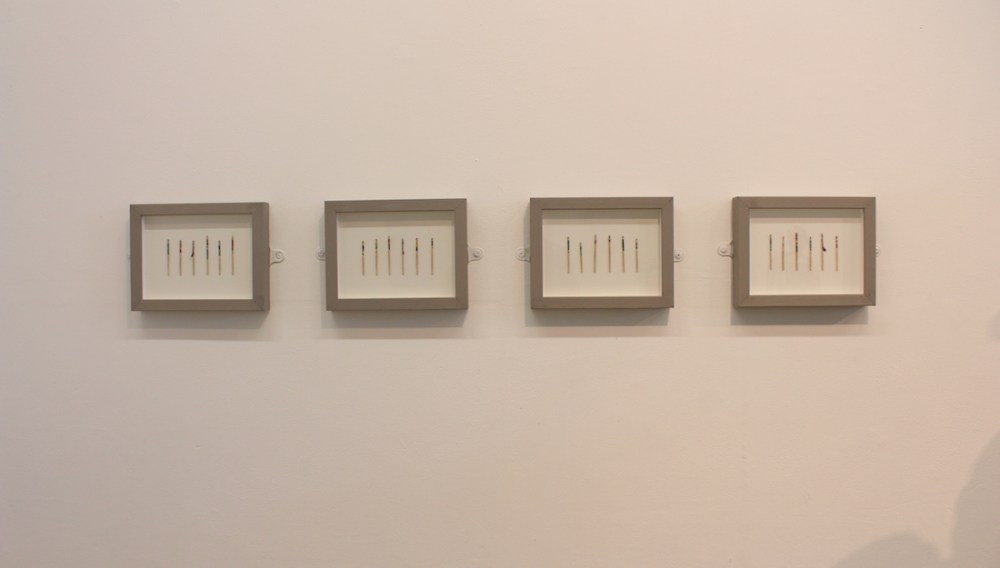 rows of painted toothpicks displayed in 4 frames on a wall