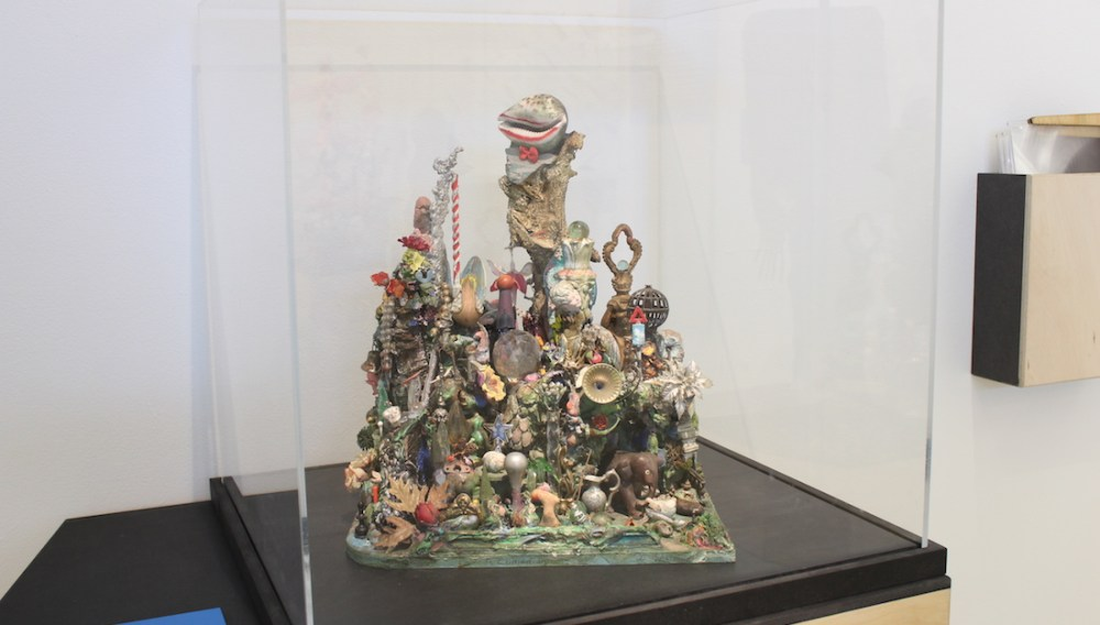 sculpture made from assembling various objects and trinkets in an exhibition case