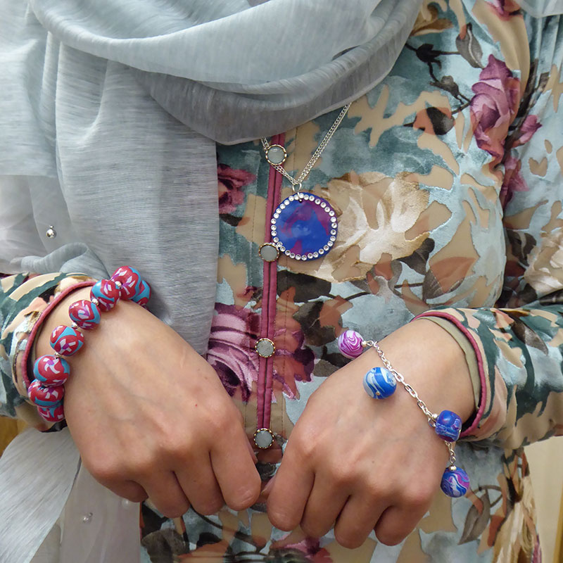 a woman wears the jewellery she had made.