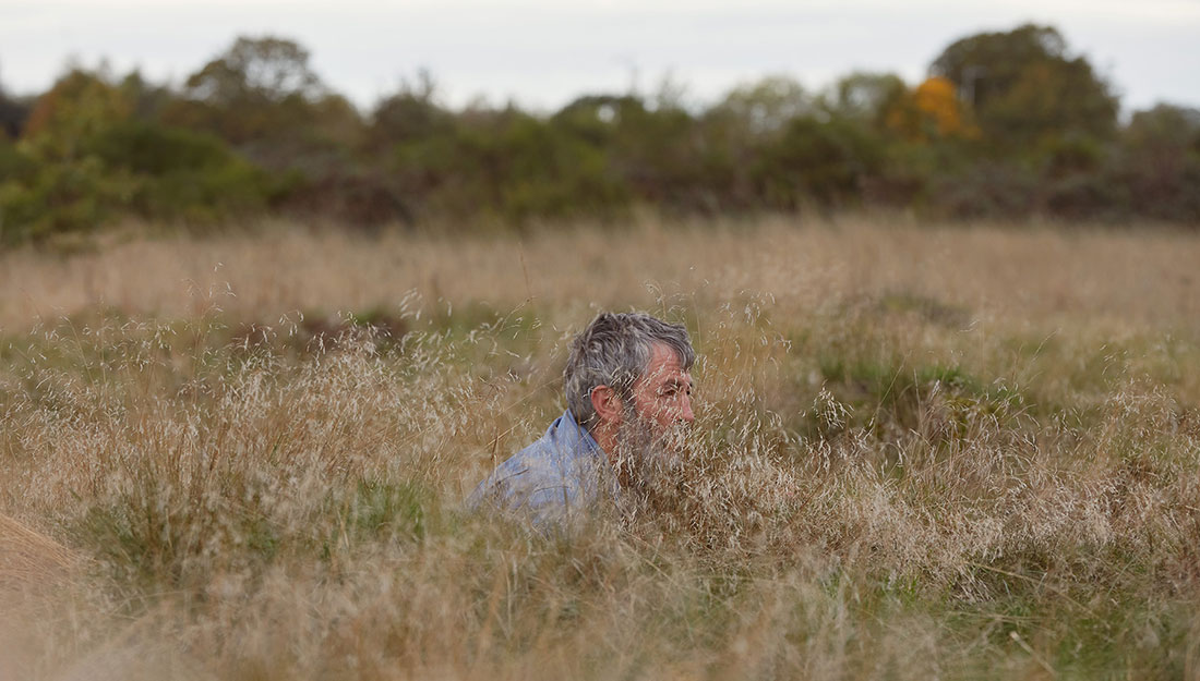 The artist, a middle aged man, crouches in the very long grass.