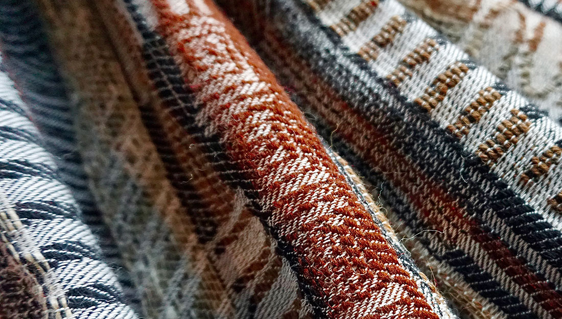 Woven fabric with a geometric and natural coloured design.