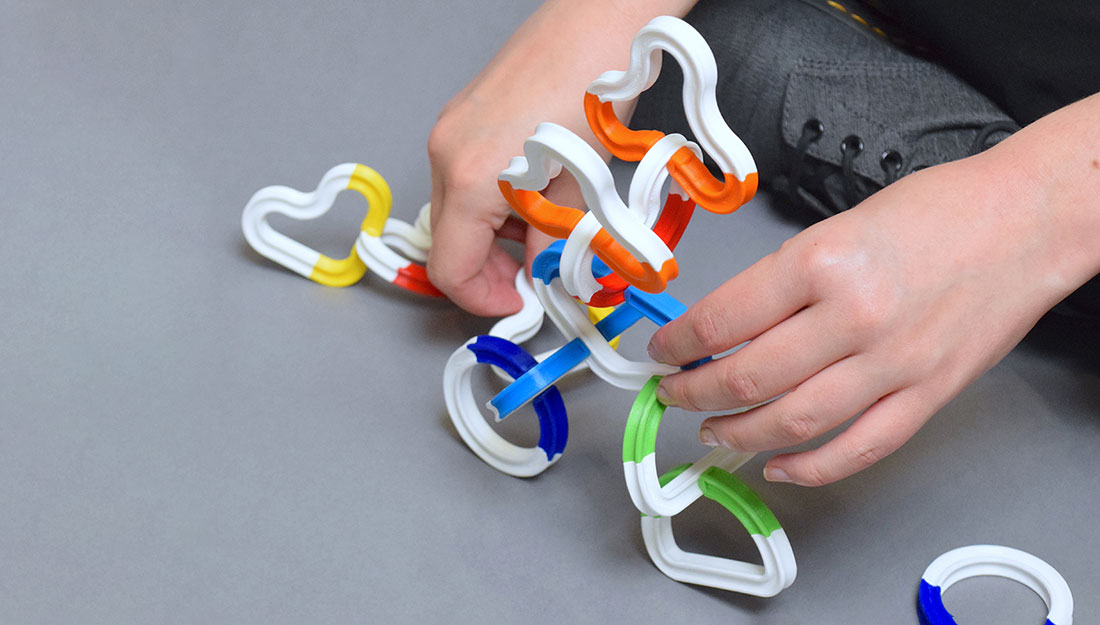 hands play with sculpture components made of brightly coloured chainlike pieces.