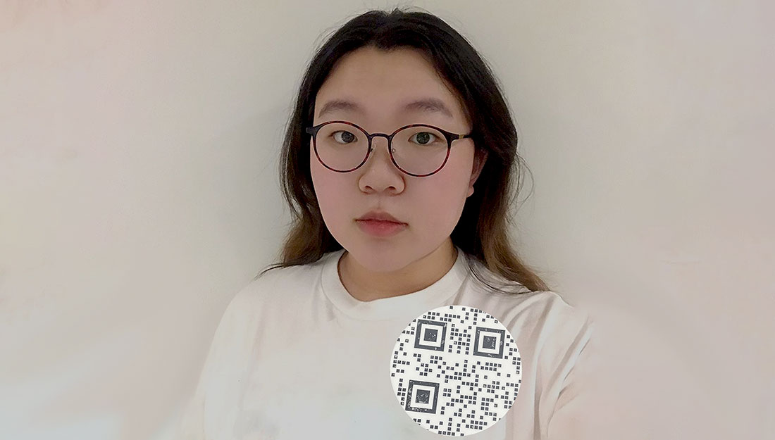 A woman wears a brooch with a QR code design.