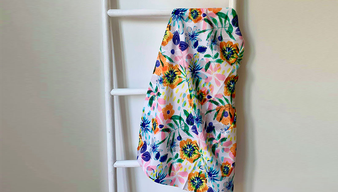 A flowery fabric hangs on a white ladder.