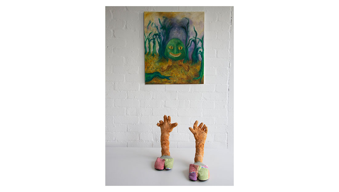 Two sculptured hands reach up form the floor and a painting of a green monster hangs nearby.