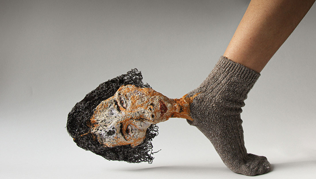 A sock with a textile embroidered head protruding from the heel.