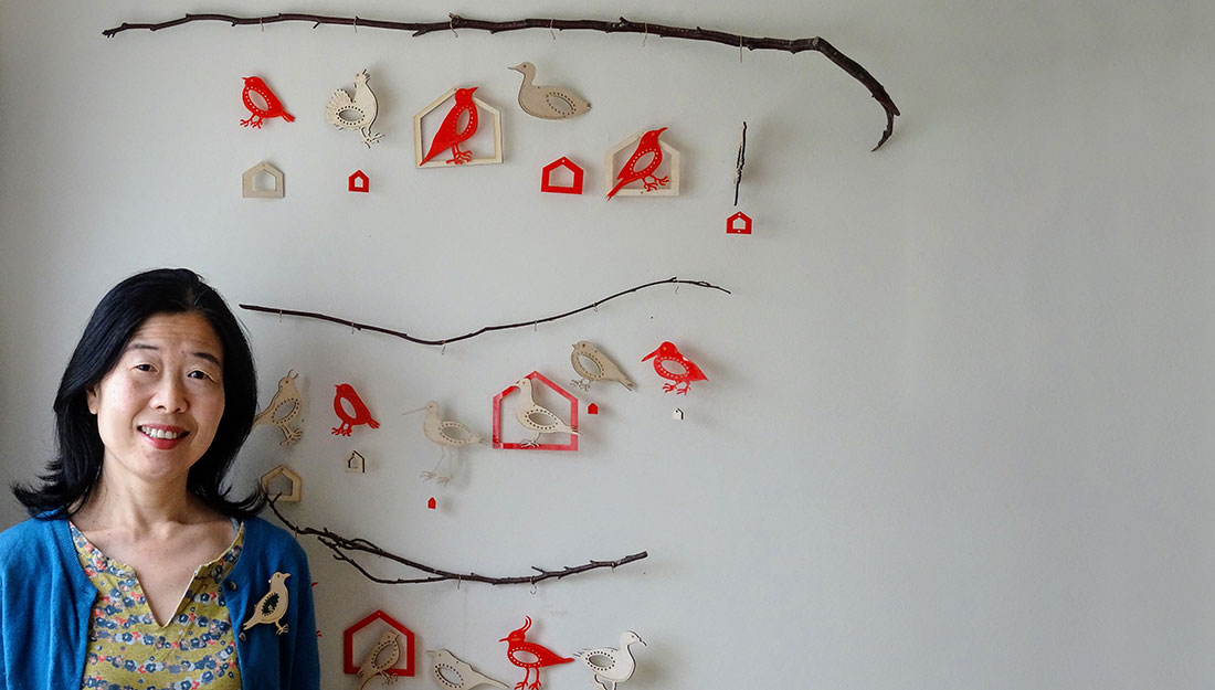 The artist stands in front a wall with hanging bird and house shapes.