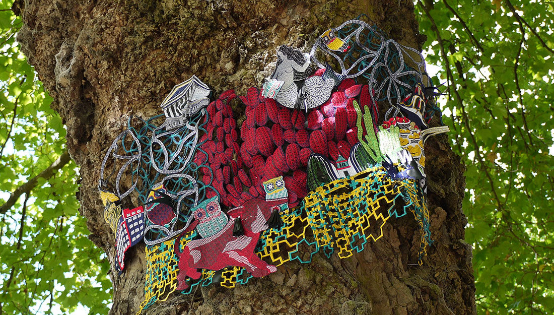 An embroidered artwork of Birmingham landmarks is displayed on a treetrunk.