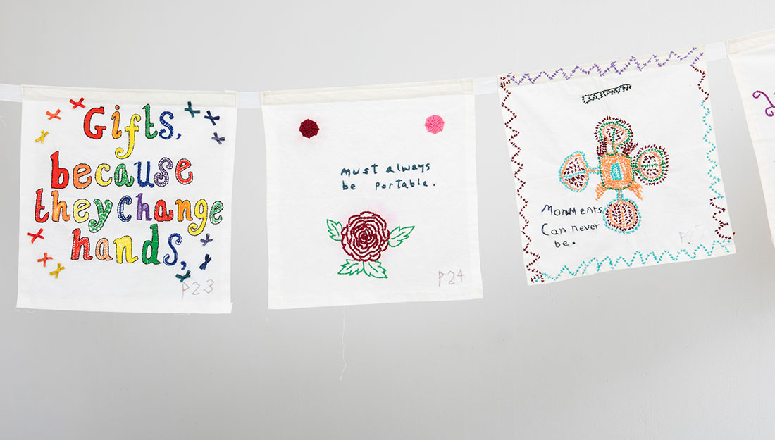 A set of embroideries hang from a ribbon. The embroidered words form part of a sentence.