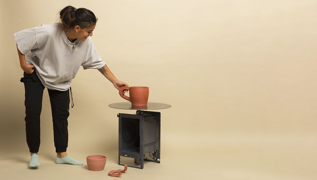 a woman stands near a machine which has a newly thrown clay pot on top.
