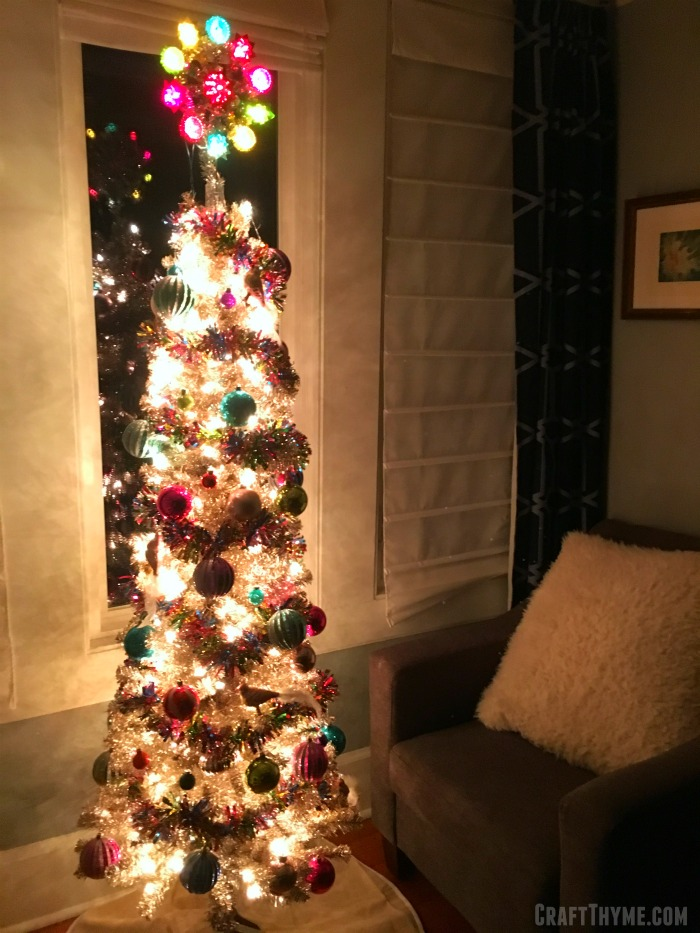 Colorful decorated tinsel tree at night