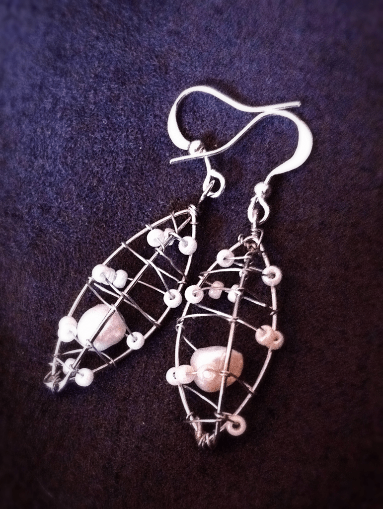 silver earrings with 3-sided pods wrapped in wire and pearl seed beads with a freshwater pearl inside