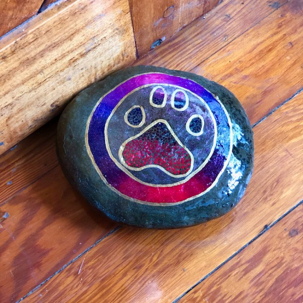 Natural rock with animal paw design in purple and pink placed as a door stop