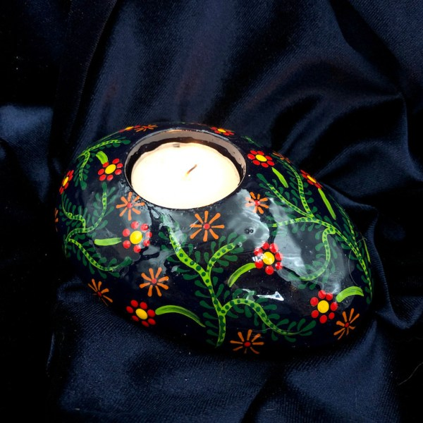Oval tea light holder with folk art flowers pattern with candle on dark background
