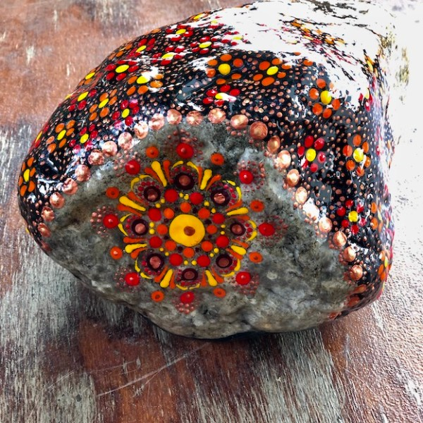 Natural rock door stop with orange, red, yellow and copper colour mandala design back