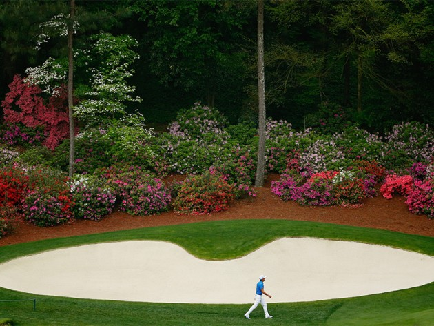 Rickie Fowler walks alongside the huge greenside bunker at the par 5 13th