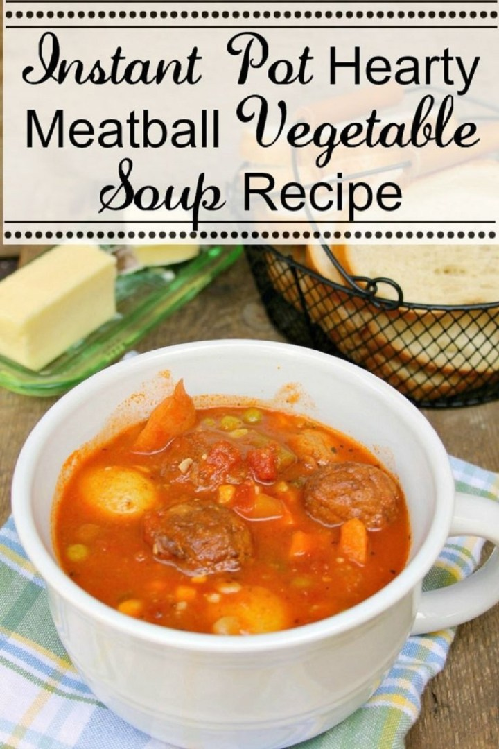 Instant Pot Hearty Meatball Vegetable Soup Recipe in a white bowl next to bread in a basket and butter on a green glass dish