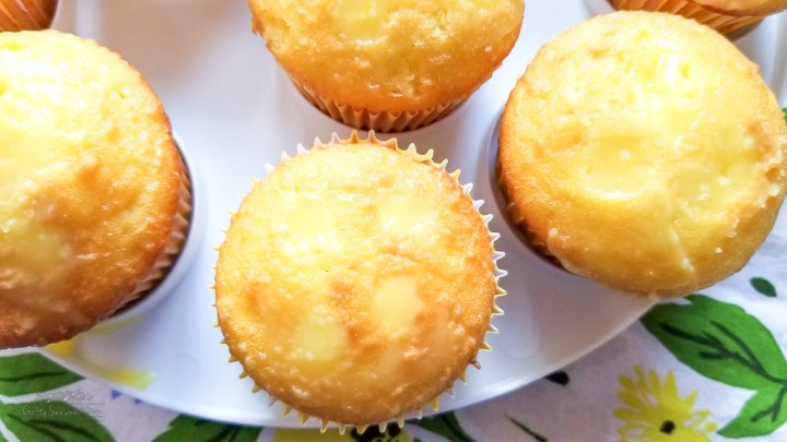 lemon cupcakes filled with lemon pudding for the Double Lemon Jello Pudding Poke Cupcakes Recipe on a floral napkin