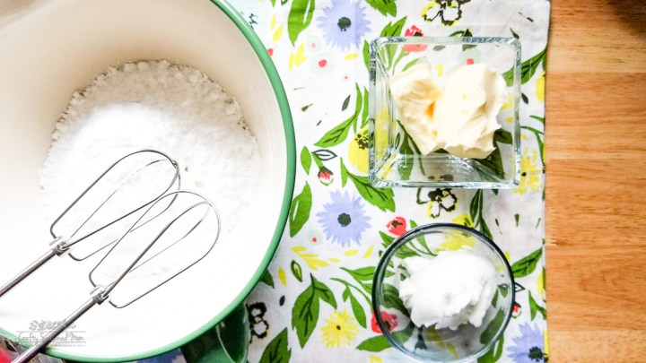 powdered sugar in a large mixing bowl next to a square glass bowl of butter and a small roud glass bowl of shortening for the Double Lemon Jello Pudding Poke Cupcakes Recipe on a floral napkin