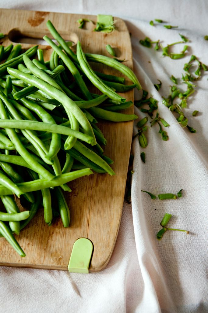 Green beans on a wooden cutting board.