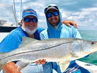 Capt. Bouncer Smith, left, keeps his customers smiling with memorable catches like this snook. (Courtesy Bouncer Smith)