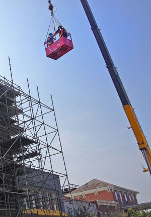 Workers suspended from crane begin work on firegutted