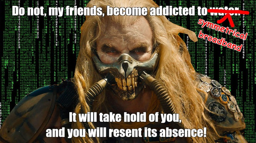 A meme-style image of Immortan Joe from Mad Max: Fury Road. Joe is superimposed over a 'Matrix waterfall' cyberspace background. The image is captioned 'Do not, my friends, become addicted to water. It will take hold of you, and you will resent its absence!' The word 'water' has been crossed out and replaced with the words 'symmetrical broadband,' set in Comic Sans.