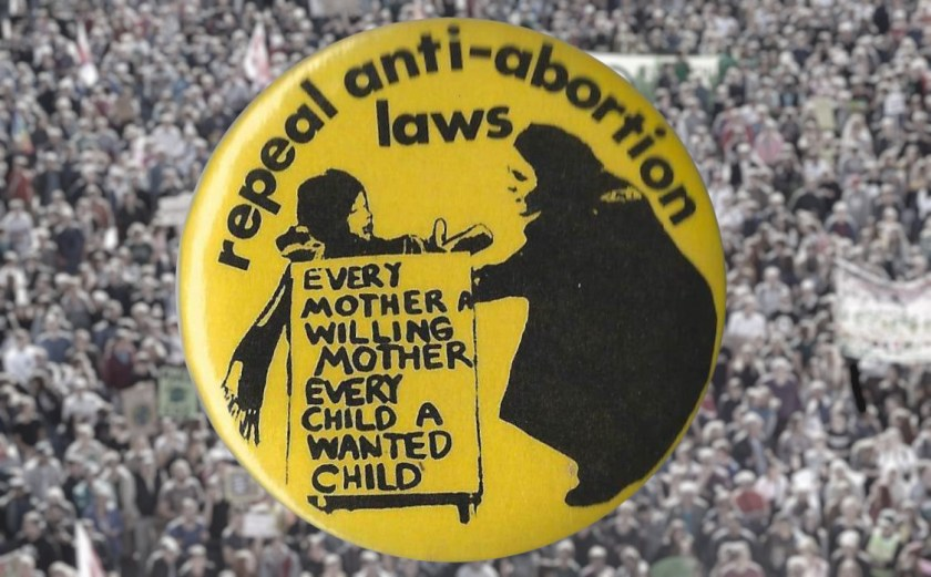 A vintage 'repeal anti-abortion laws/every child a wanted child, every mother a willing mother' protest badge, superimposed over a large, blurry crowd of protestors.
