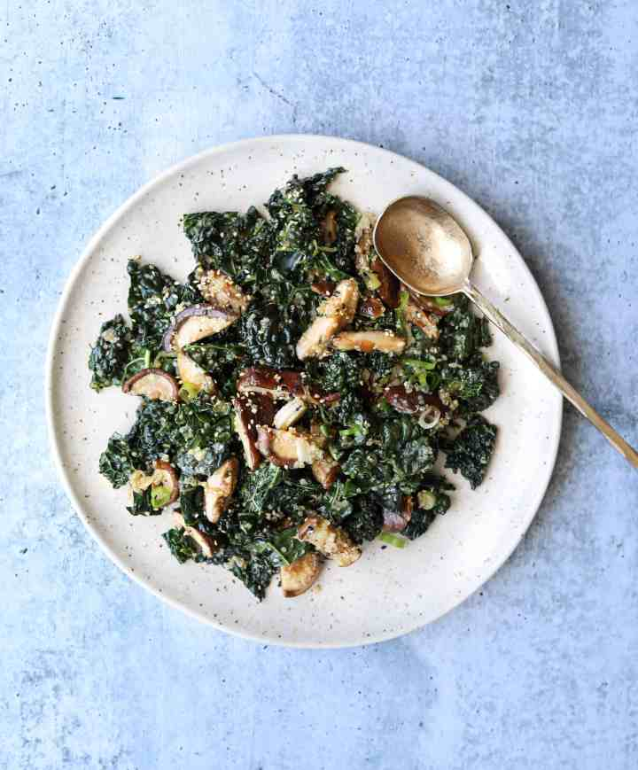 Kale and Quinoa Salad on a white plate with a gold spoon