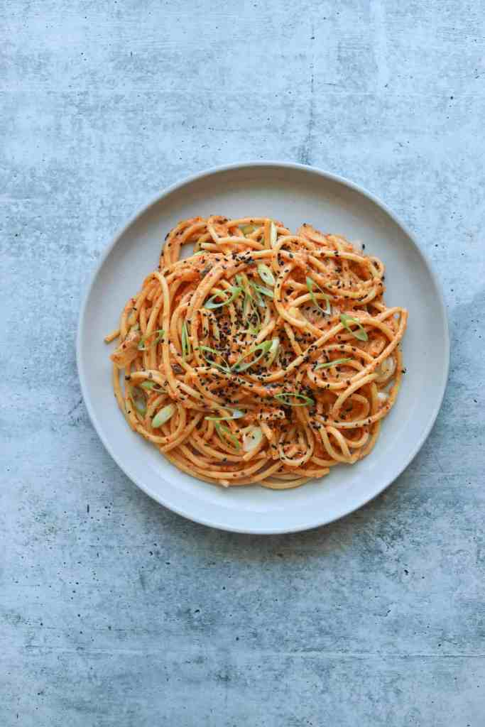 Kimchi Carbonara on a white plate with sesame seeds and scallions