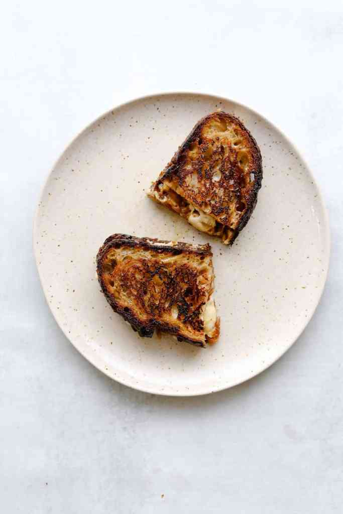 Golden brown White Cheddar + Fig Grilled Cheesegrilled cheese on a white plate