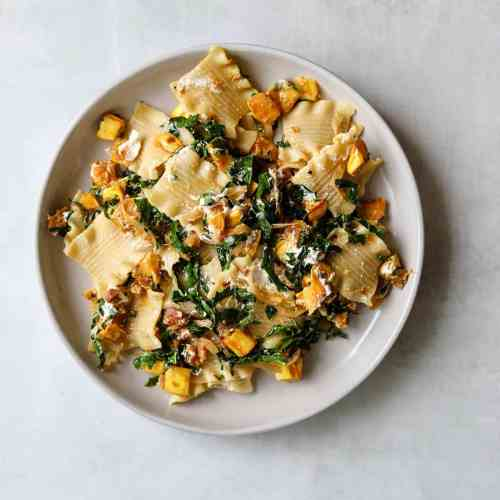 The Perfect Fall Pasta with Pancetta, Squash, Goat Cheese + Kale on a white plate