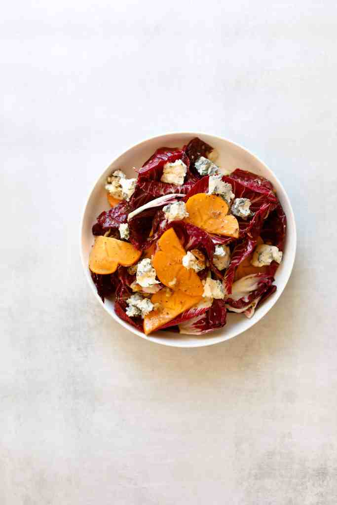 Persimmon + Blue Cheese Salad with Grainy Mustard Vinaigrette in a bowl