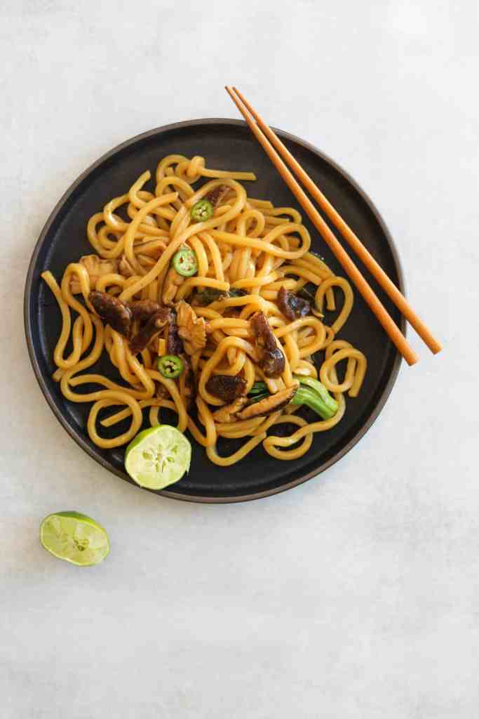 Udon noodle stir fry on a black plate with chop sticks