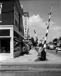 "This looks north across the railroad tracks on North Sandusky at Walthers Hardware at the ""Sign of the Big Saw"", probably about the 1940s. Contributed by Jim Croneis."