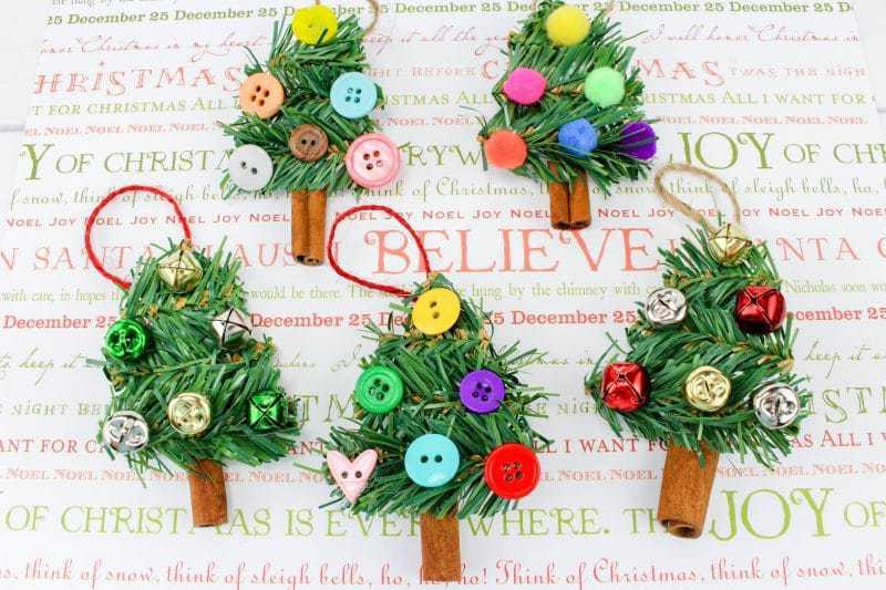 A fun DIY Christmas Tree Ornament craft, made using wreath garland, cinnamon sticks, twine, buttons, pom poms and jingle bells.