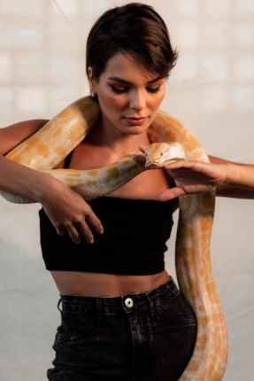 young serious woman with snake on neck