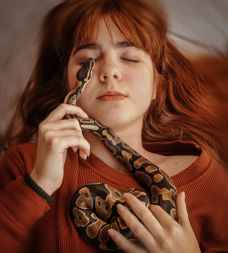 woman in knit sweater holding a snake