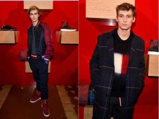 Presley Gerber (esq.) vestiu uma malha azul, uma bomber jacket preta com mangas vermelhas, um tracksuit preto e tênis de camurça vermelho, todos da Hilfiger Edition. Enquanto isso,