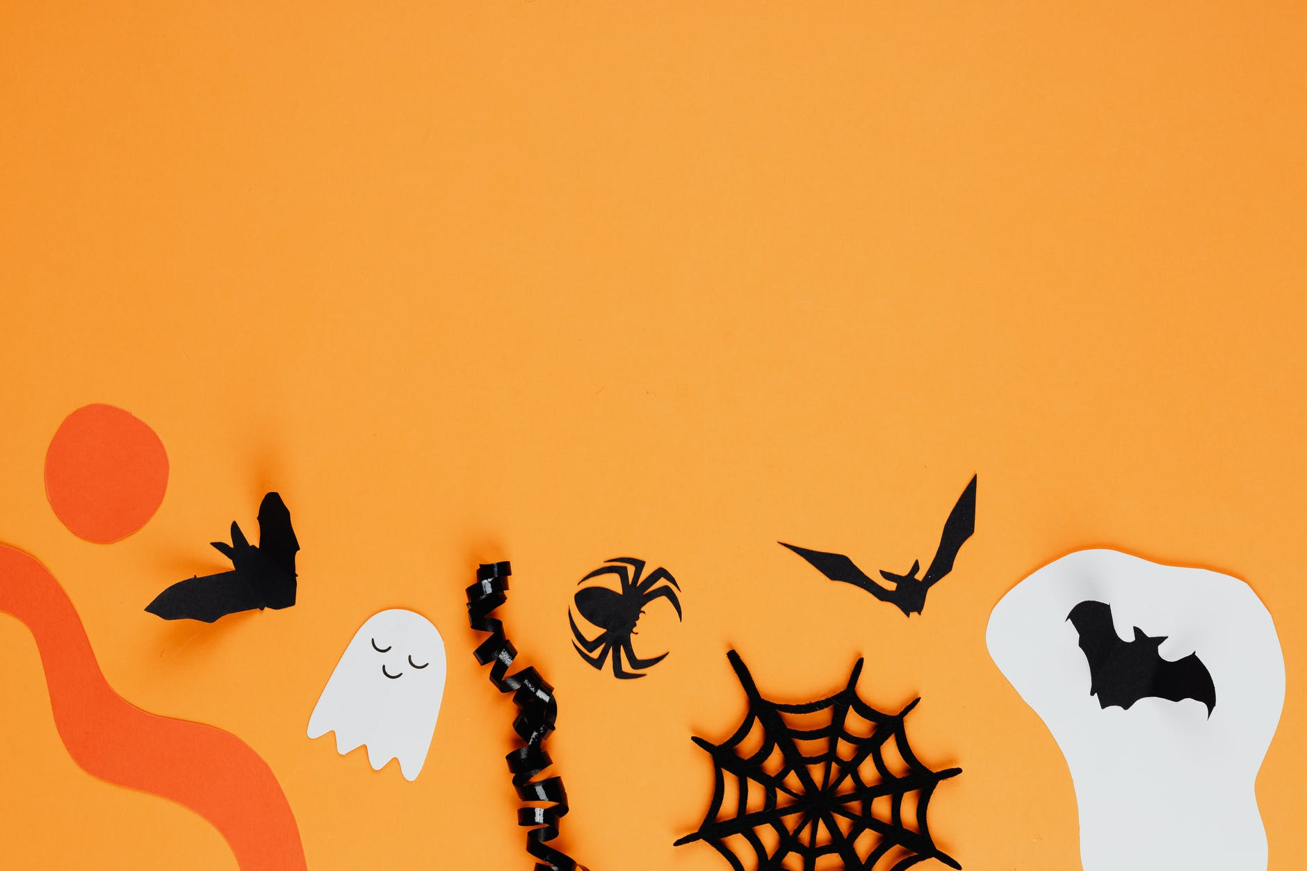 paper halloween decorations on an orange background