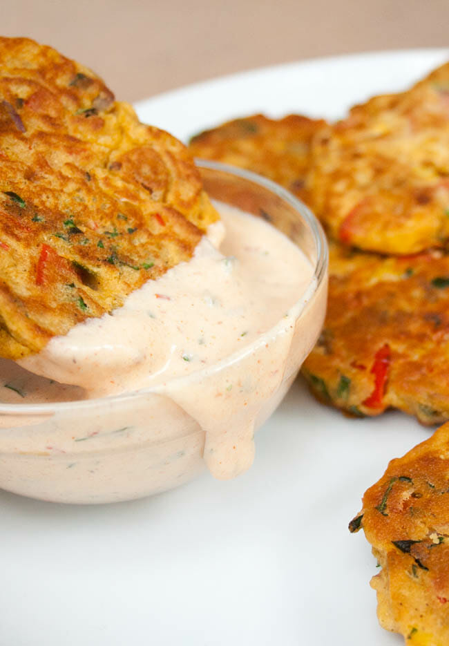 Vegetable Fritter being dipped into Vegan Chipotle Ranch Dressing. More Vegetable Fritters in background.