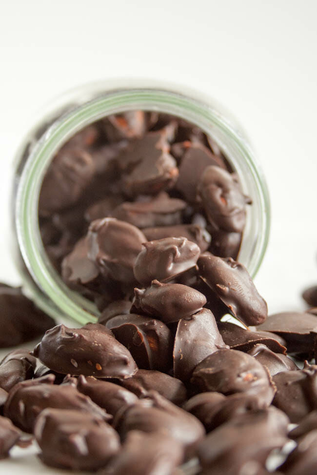 Vegan Mexican Chocolate Covered Almonds spilling out of jar.