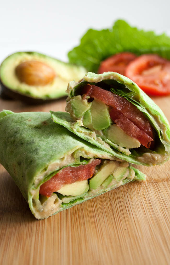 ALT (Avocado, Lettuce, and Tomato) Wrap stacked with avocado, lettuce, and tomato in the background.