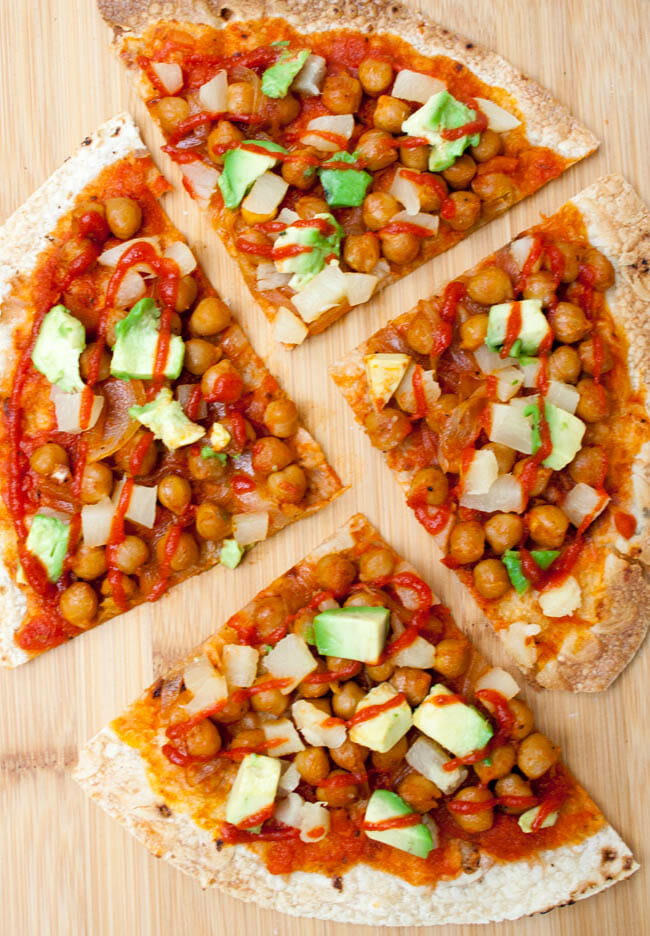 Maple Sriracha Chickpea and Pineapple Tortilla Pizza slices on a cutting board.