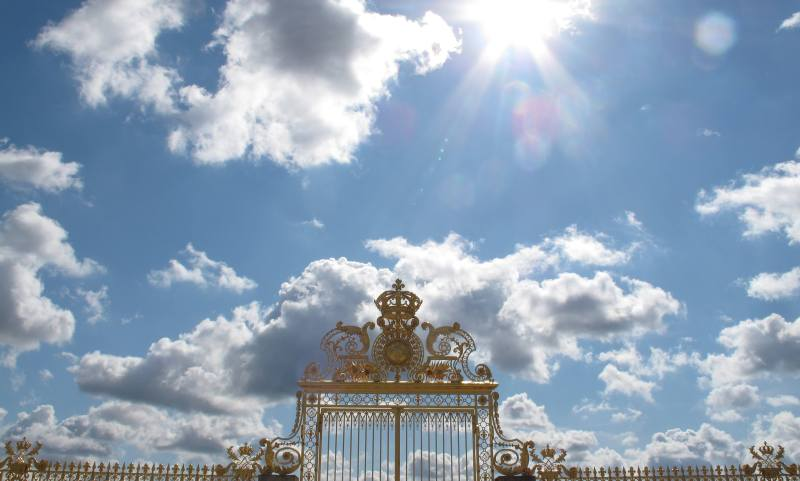 Gold Gates of Versailles with a Vibrant Blue Sky and Sun Flare