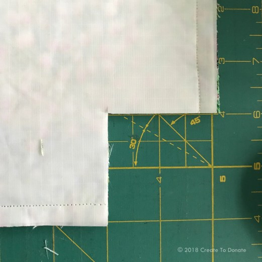 Picture showing how to cut a two inch square from edge of the toiletry bag to start creating the bottom of the bag.