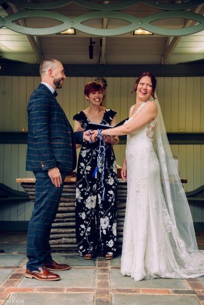 Claire conducting a handfasting during a wedding ceremony, photo by Fiona Walsh Photography